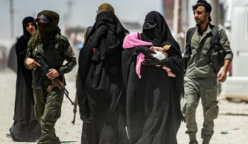 An internal security patrol escorts women, reportedly wives of Islamic State fighters, in the al-Hol camp in al-Hasakeh, Syria, July 23, 2019.