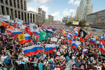 People with national flags and various political party flags gather during a protest in Moscow, Russia, July 20, 2019.
