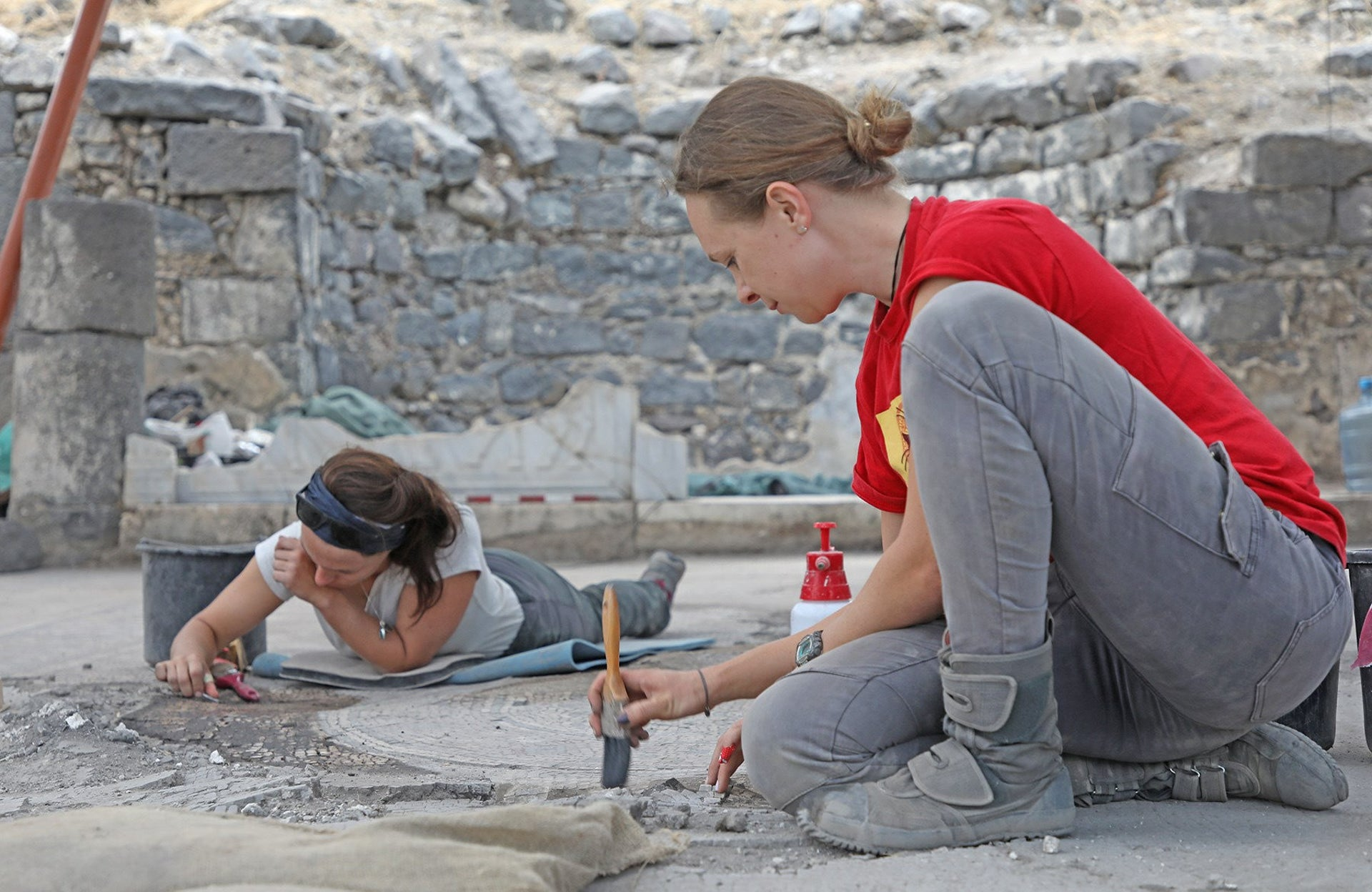 Conservators Yana Vitkalov and Nina Koskanen carefully cleaning the mosaic carpet of the Burnt Church