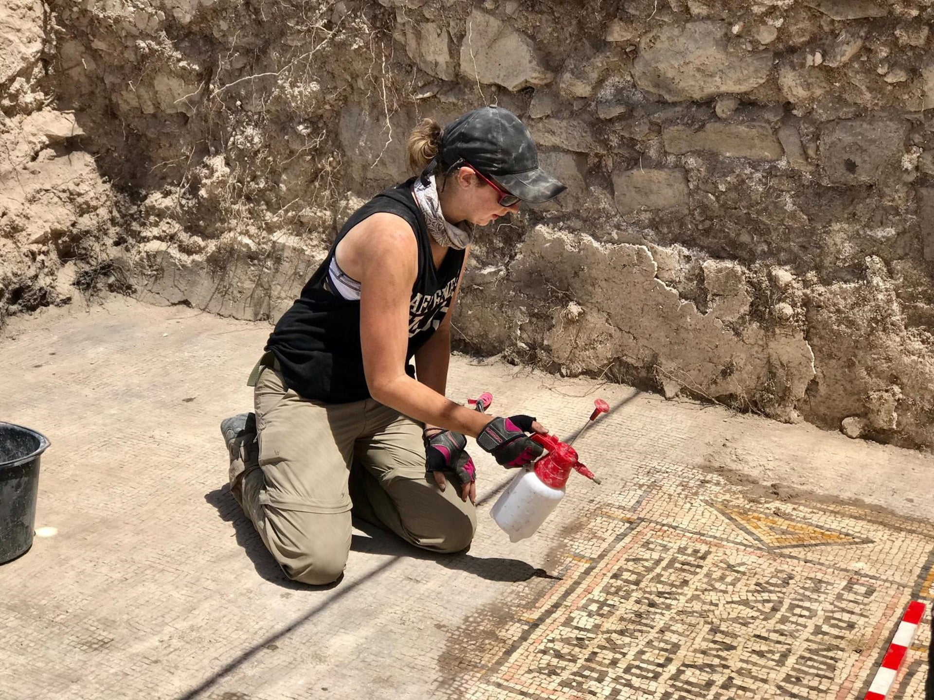 Jessica Rentz, area supervisor, cleaning an inscription written in bad Greek in the Burnt Church, Hippos-Sussita