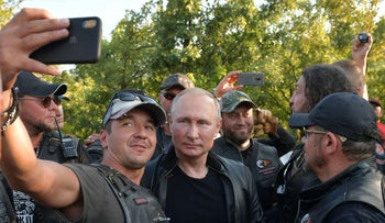 """Russian President Vladimir Putin poses with members of the """"Night Wolves"""" motorcycle club in Sevastopol, Crimea"""