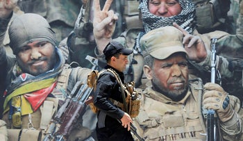 A members of Iraqi Popular Mobilization Forces (PMF) walks past a poster of PMF members at Popular Mobilization Forces Media Center in Baghdad, Iraq, July 2, 2019