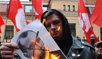 An activist burns a crossed-out portrait of Stepan Bandera during a rally in support of ethnic Russians in the Crimea and Eastern Ukraine, in St. Petersburg, Russia, March 3, 2014.