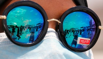 Muslim pilgrims are reflected on a pilgrim's sunglasses as they walk to cast stones at a pillar in the symbolic stoning of the devil near Mecca, Aug. 13, 2019.