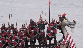 Members of the Viking Jarl Squad pose for pictures with a Viking Galley ship on the morning of the annual Up Helly Aa Festival, in Lerwick, Shetland Islands, on January 26, 2010.