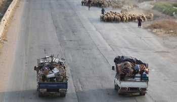 Syrian families fleeing battles with trucks loaded with their belongings in the southern Idlib province on August 14, 2019.