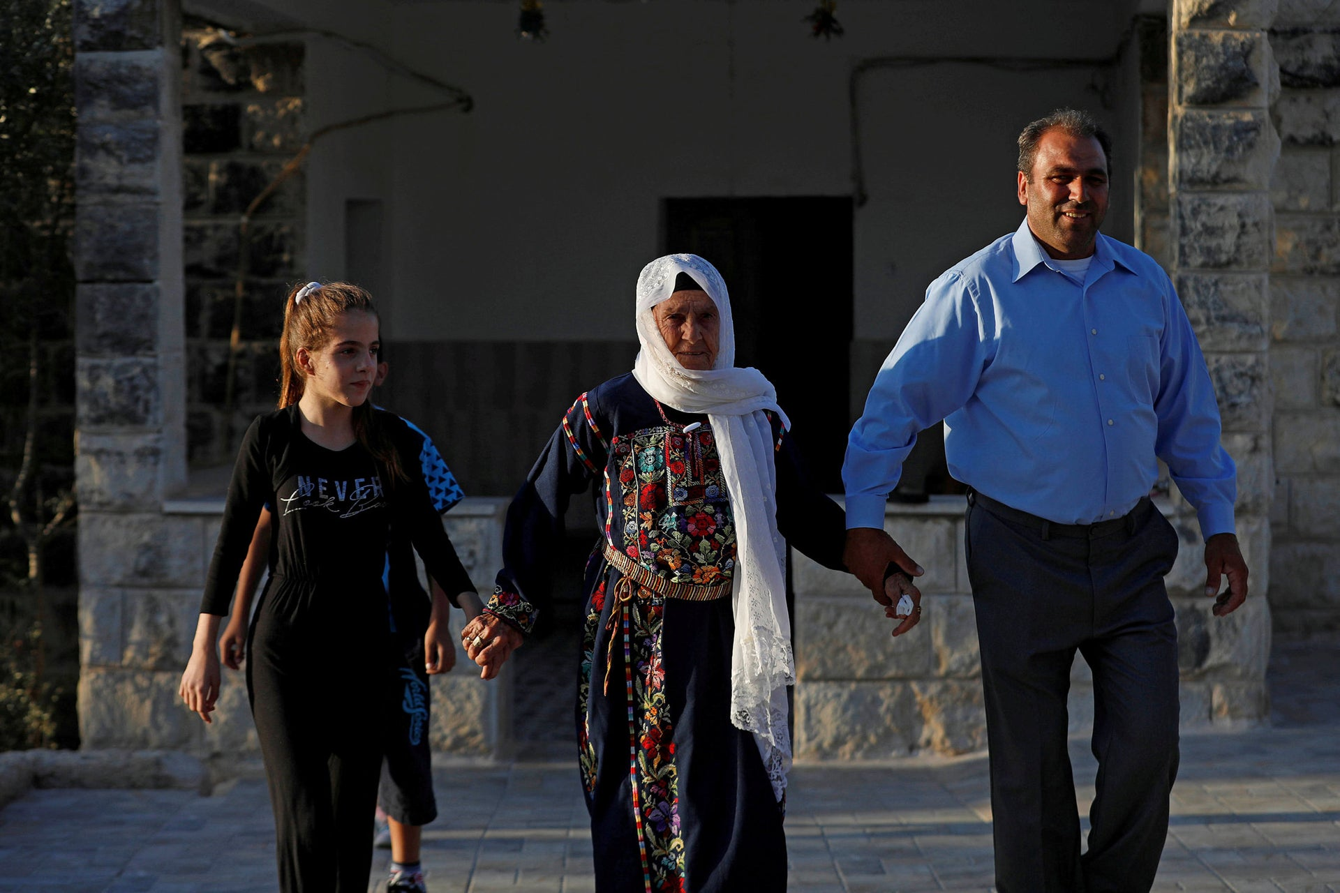 Muftia, the grandmother of U.S. congresswoman Rashida Tlaib, walks with her son and her granddaughter outside her house in the village of Beit Ur Al-Fauqa in the West Bank, August 16, 2019.