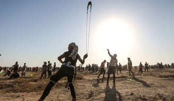 A Palestinian protester uses a slingshot to hurl stones during clashes with Israeli forces near the fence along the border with Israel in the Gaza Strip on August 16, 2019.