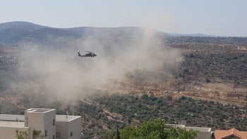 An Israeli army helicopter flies over the West Bank settlement of Dolev, August 23, 2019