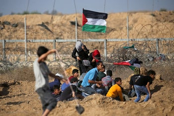 Palestinian demonstrators take cover at the border fence in the southern Gaza Strip, June 21, 2019.