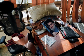 A poster of Hezbollah leader Sayyed Hassan Nasrallah amid other damage inside the media office in Beirut, Lebanon, August 25, 2019.