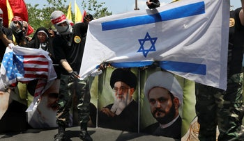 A demonstrator holds a representation of the Israeli flag which is set on fire during the annual Quds, or Jerusalem Day rally in Tehran, Iran, May 31, 2019.