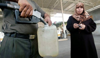 File photo: A Palestinian fills a fuel container in the Gaza strip, October 2007.