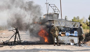 A Popular Mobilization Forces member stands by a burning truck after a drone attack in Anbar Province, Iraq, August 25, 2019.