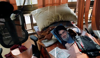 A poster of Hezbollah leader Nasrallah is seen amid other damage inside the media office in a stronghold of Hezbollah in a southern suburb of Beirut, Lebanon, August 25, 2019.