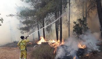 Firefighters work in the Beit Shemesh area, August 26, 2019.