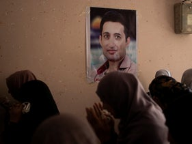 Relatives of Palestinian activist Tamer al-Sultan mourn next to a photo of him on a wall in his family home during his funeral in town of Beit Lahiya, Gaza Strip, August 25, 2019.