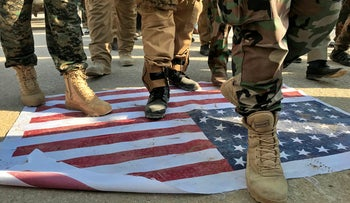 Mourners step over the print of a U.S. flag during the funeral procession of Abu Ali al-Dabi, a fighter of Iran-backed PMF, during his funeral procession in Baghdad, Iraq, August 26, 2019.