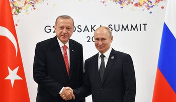 Russian President Vladimir Putin, right, and Turkish President Recep Tayyip Erdogan shake hands after a meeting on the sidelines of the G-20 summit in Osaka, Japan, June 29, 2019.