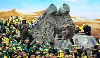 Members of Lebanon's Shi'ite movement Hezbollah parade with a mock missile launcher in the southern Lebanese city of Nabatiyeh, on October 27