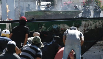 Masked Palestinian protesters take cover while throwing stones at Israeli security forces amidst clashes following Friday prayers in the East Jerusalem Arab neighborhood of Isawiyah, June 28, 2019.