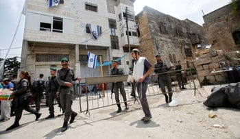 Israeli border police officers are seen in front of a disputed building in the West Bank city of Hebron on July 26, 2017.