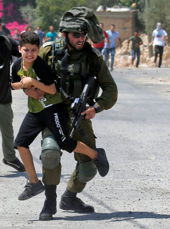 An Israeli soldier temporarily detains a Palestinian youth in the village of Kfar Qaddum, West Bank, August 23, 2019.