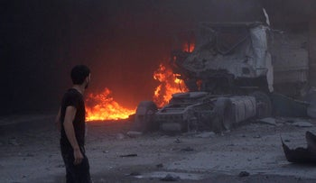 A man looks at burning cars after air strikes hit the northern town of Maaret al-Numan, in Idlib province, Syria, August 28, 2019.