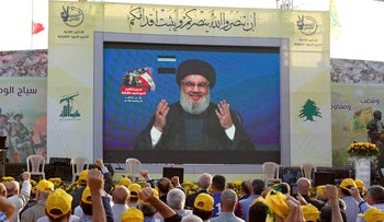 Hezbollah leader Hassan Nasrallah addresses his supporters via a screen during a rally in al-Ain village, Lebanon August 25, 2019.