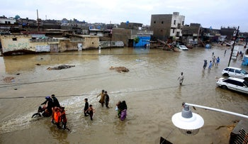 People wading through a flooded street after a heavy rainfall in Karachi, Pakistan, July 30, 2019.