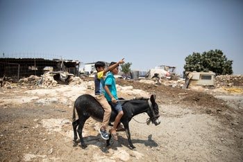 Two Palestinian boys riding a donkey in the village of Khirbet Sussia in the West Bank.