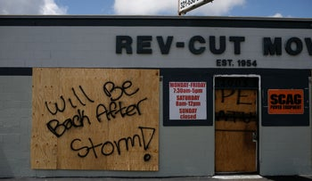 """A boarded-up business with """"Will be back after storm"""" painted on it ahead of the arrival of Hurricane Dorian in Cocoa, Florida, September 1, 2019."""