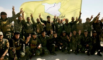 U.S.-backed Syrian Democratic Forces fighters pose for a photo in Baghouz, Syria, after the SDF declared the area free of Islamic State militants, March 23, 2019.