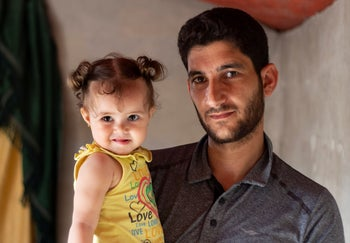 "Abdel Hamid al-Yousef with his 11-month-old daughter Aya, at a displaced settlement near the Turkish border called ""Mokhayyam al-Karamah,"" September 1, 2019."
