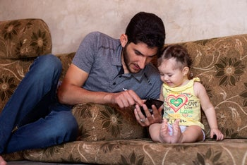 "Abdel Hamid al-Yousef plays with his 11-month-old daughter Aya, at a displaced settlement near the Turkish border called ""Mokhayyam al-Karamah,"" Arabic for ""Dignity Camp,"" September 1, 2019"