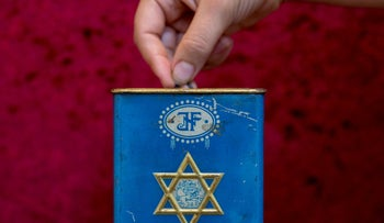 File photo: Dropping a coin into a JNF charity box, September 20, 2016.