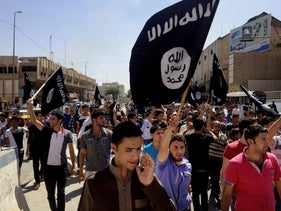 Demonstrators chanting pro-ISIS slogans as they carry the group's flags in front of the provincial government headquarters in Mosul, Iraq, June 16, 2014.