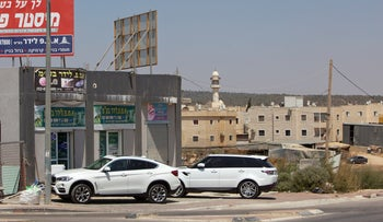 Two cars parked in the Bedouin town of Laqiya, August 24, 2019.
