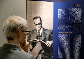 A visitor reads the biography of the late Egyptian writer Naguib Mahfouz after the opening of the Mafhouz Museum in Cairo, July 14, 2019.