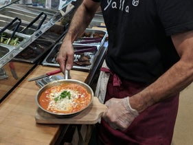 Wearing a hippie-style bandana and shirt with the restaurant's logo, Arama doesn't stop stuffing falafel into pita or adding spices to the shakshuka bubbling on a gas stove.