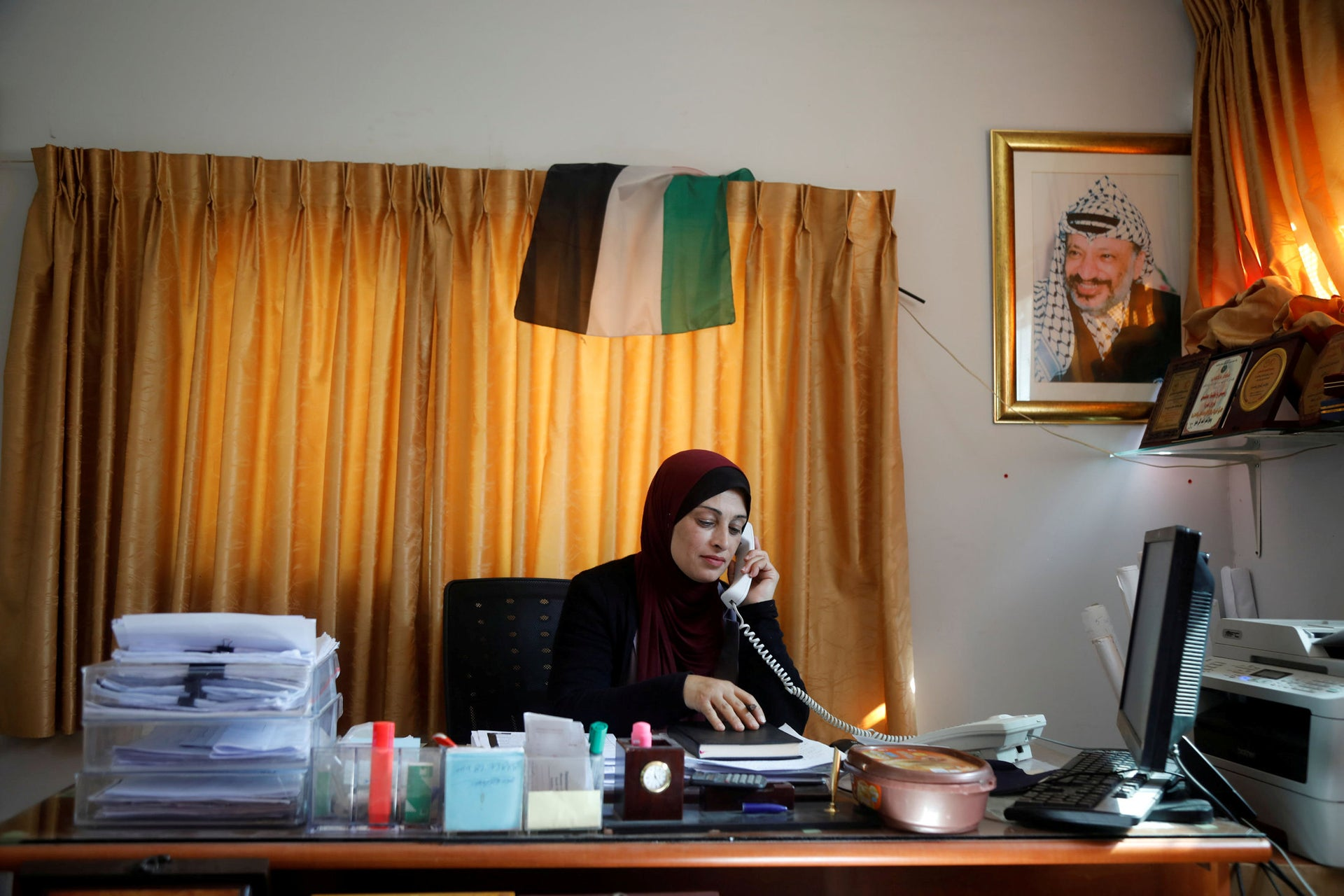alestinian woman Bothena Turabe, 47, speaks on the phone as she works from her home in the village of Sarra near the Jewish settlement of Havat Gilad, in the Israeli-occupied West Bank,
