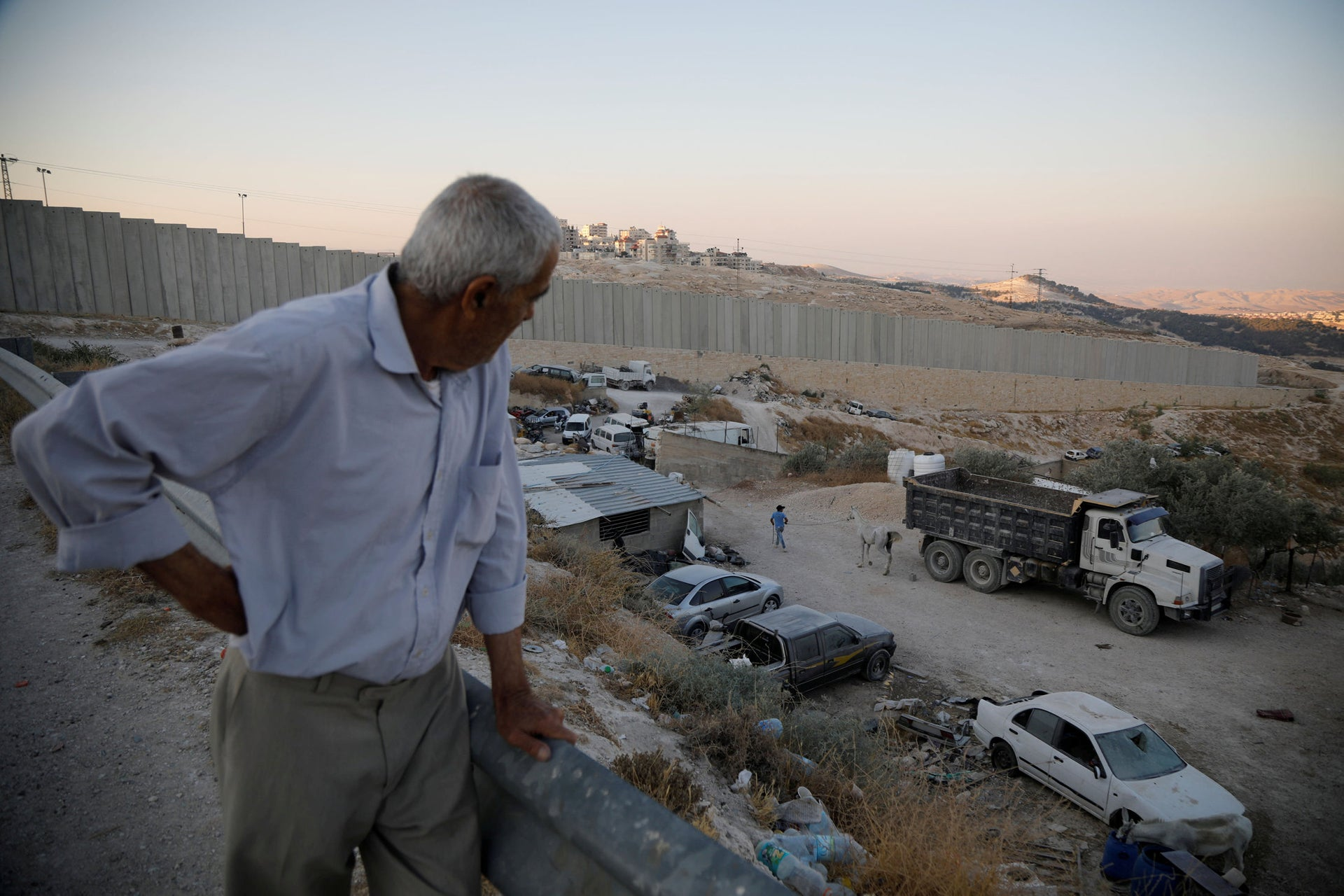 Palestinian man Ali Farun, 74, stands near a section of the Israeli barrier in al-Eizariya town close to the Jewish settlement of Maale Adumim