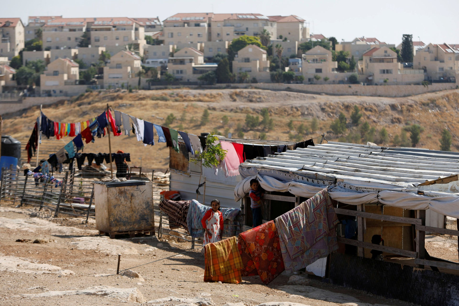 Palestinian children play outside their dwelling in al-Eizariya town with the Jewish settlement of Maale Adumim in the background