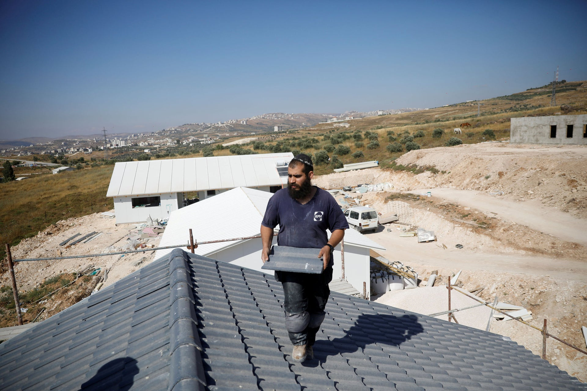 A man works on a house under construction in the Israeli settlement of Havat Gilad