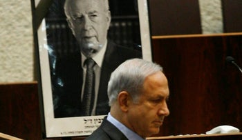 Netanyahu in front of a picture of slain Prime Minister Yitzhak Rabin, during a memorial session of Knesset, 2009.