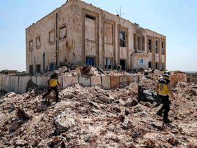 Syrian relief workers walk through the rubble outside a health facility that was hit by a reported Russian air strike in the country's northern province, August 31, 2019.