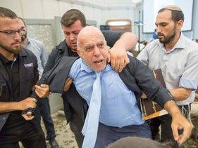 Activist Eli Yosef being removed from a conversion conference being attended by rabbis in Israel, July 18, 2018. Yosef had used the event to protest the rabbis' silence on Israeli arms sales.