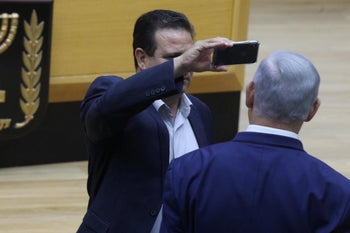 Arab lawmaker Ayman Odeh filming Prime Minister Benjamin Netanyahu in the Knesset prior to the vote on the bill to allow filming in Israeli polling stations, September 11, 2019.