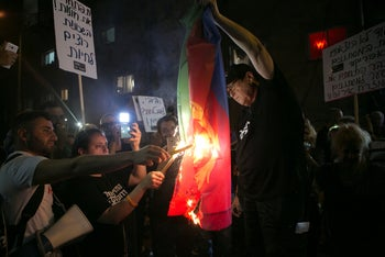 Members of the self-styled 'South Tel Aviv Liberation Front' burn an Eritrean flag, held by leader Sheffi Paz during a demonstration, Tel Aviv, August 30, 2018.