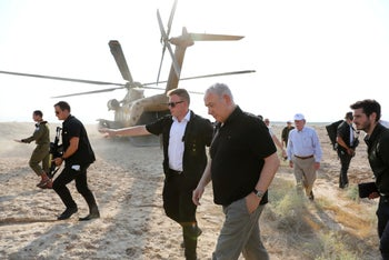 Israeli Prime Minister Benjamin Netanyahu, center, and US National Security Advisor John Bolton, back right, get off a helicopter during a visit to the Jordan Valley, on June 23, 2019.